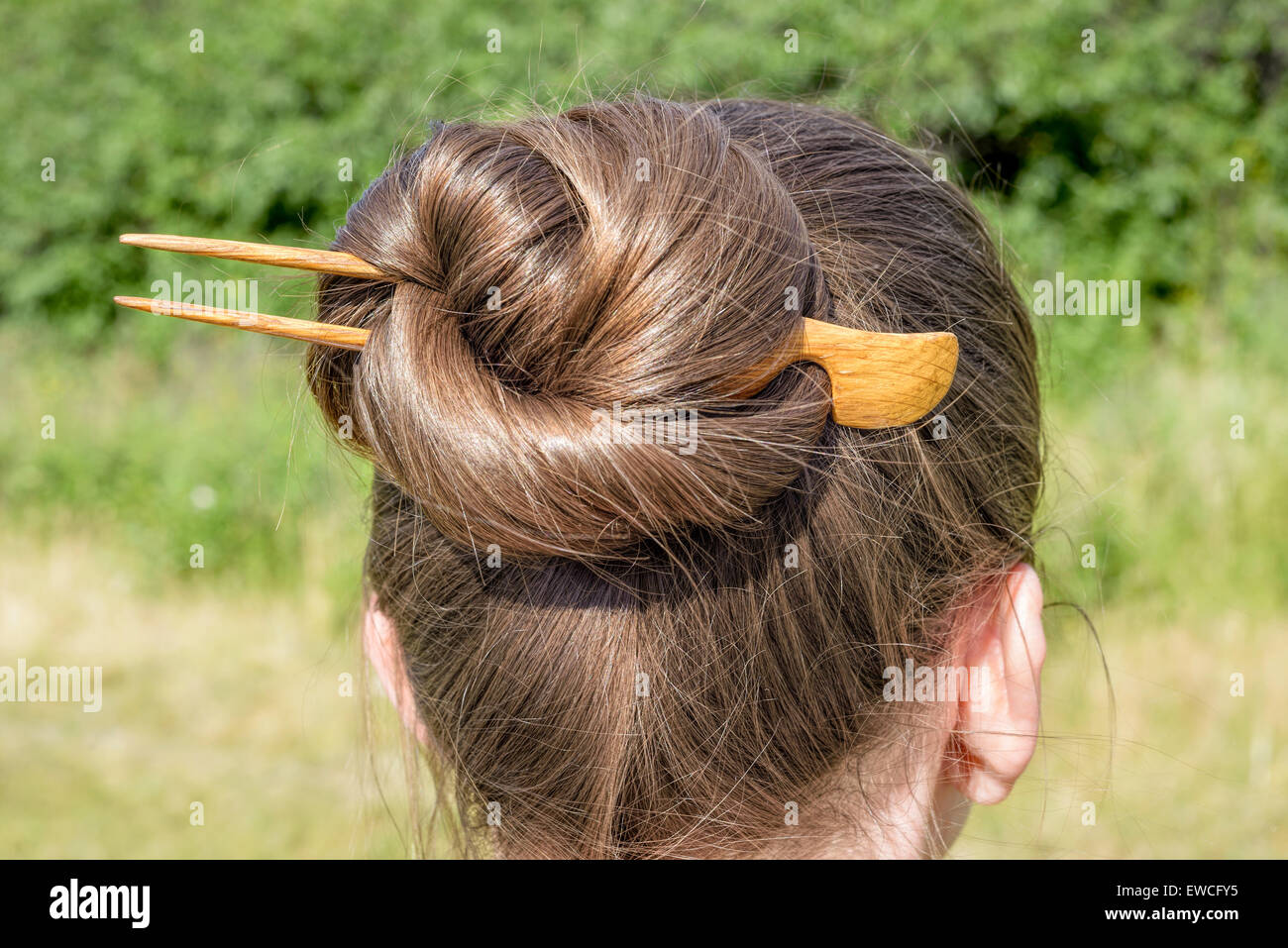 Detail of a chignon with a wooden hairpin to keep the hair attached together - Stock Image