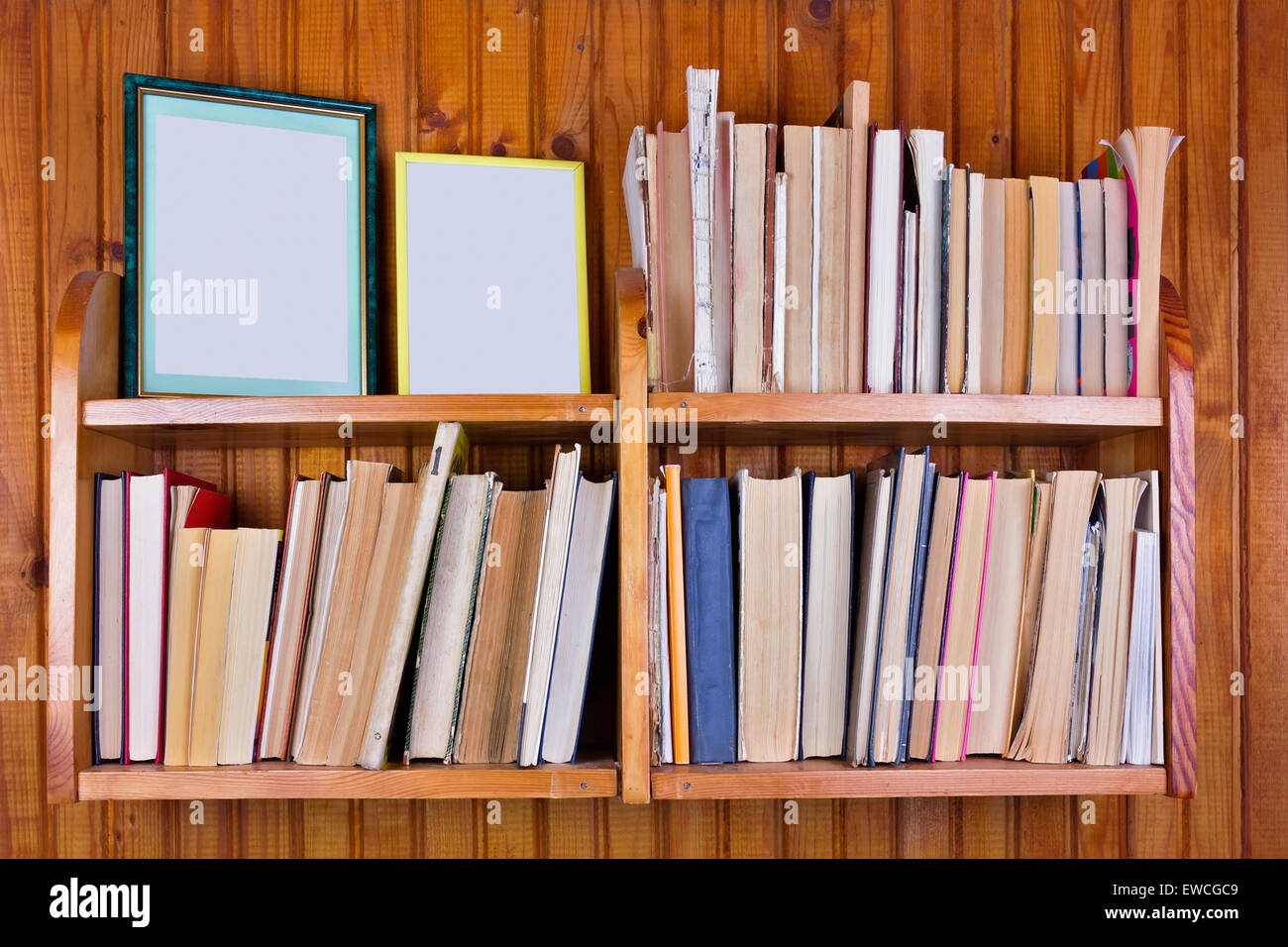 The old forgotten decrepit books and photos on the wooden shelf. The wall of the rural house is upholstered with - Stock Image