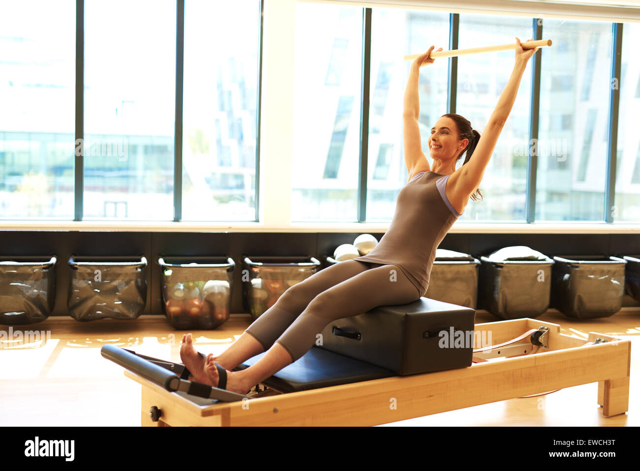 Healthy Smiling Brunette Woman Wearing Leotard and Practicing Pilates in Exercise Studio - Stock Image