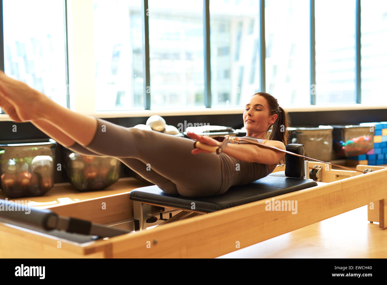 Healthy Smiling Brunette Woman Wearing Leotard Practicing Pilates in Bright Exercise Studio - Stock Image