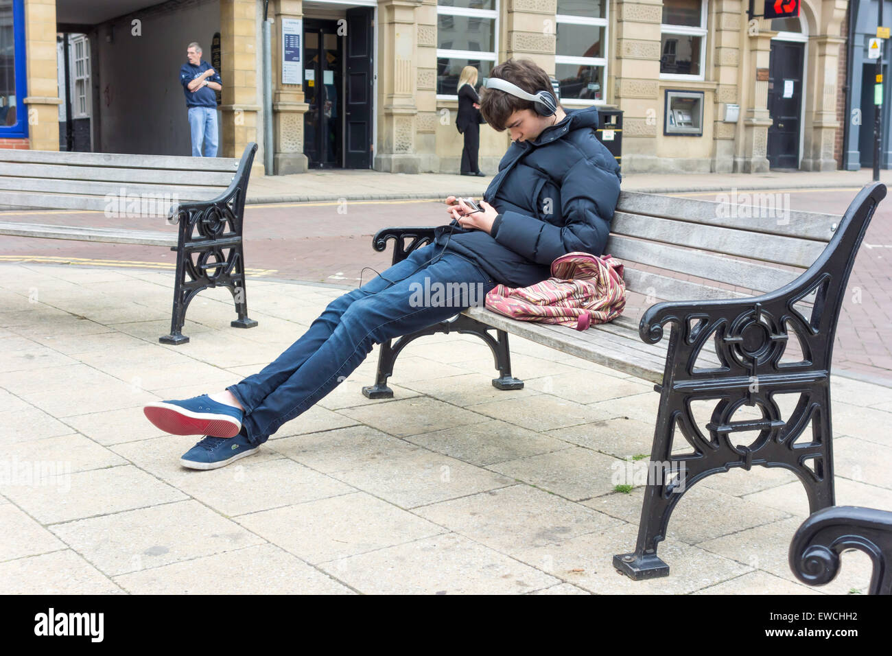 Town Centre young man oh a seat with headphones engrossed in his mobile phone telephone - Stock Image
