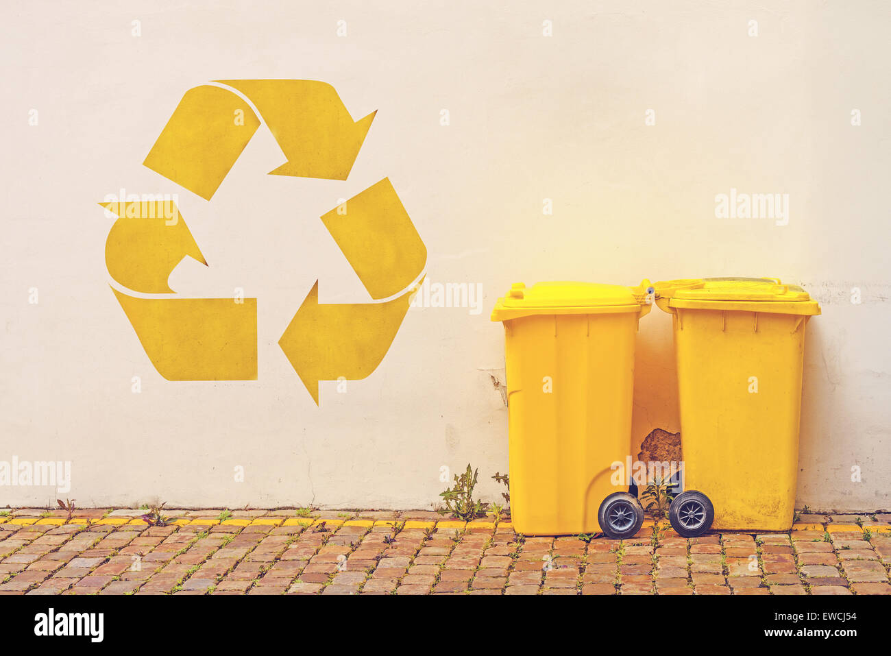 Two Yellow Plastic Recycle Bins on the Street Against White Wall with Recycle Symbol Stencil Graffiti, Toned Image - Stock Image