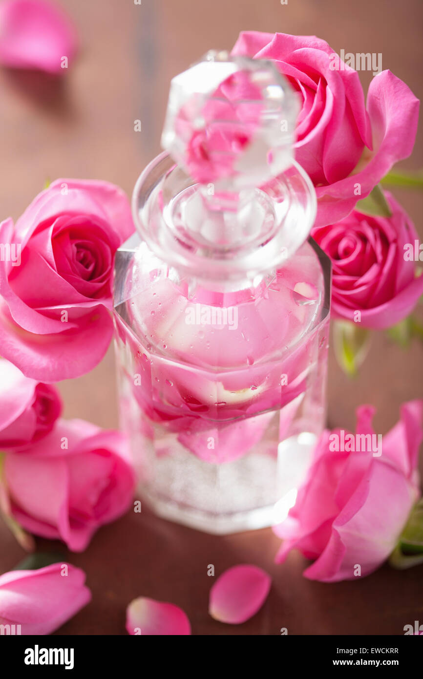 perfume bottle and pink rose flowers. spa aromatherapy - Stock Image