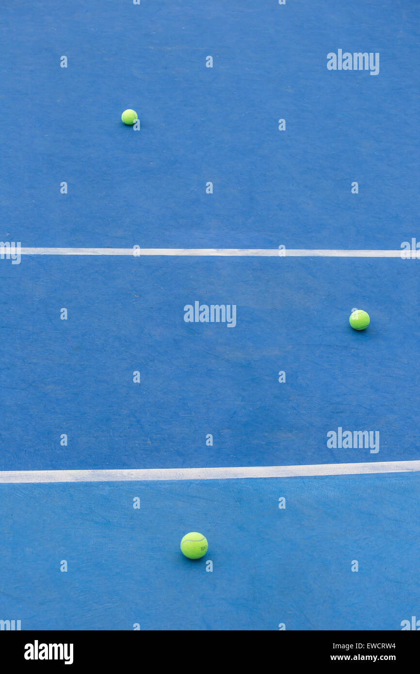 Blue tennis court with  three yellow balls on the floor - Stock Image