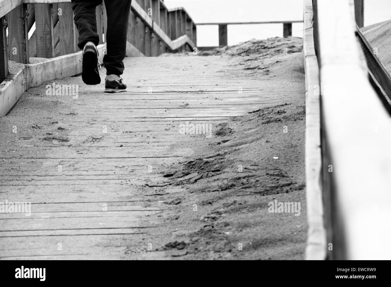 A lonely boy walking on a wooden bridge near the sea stock image