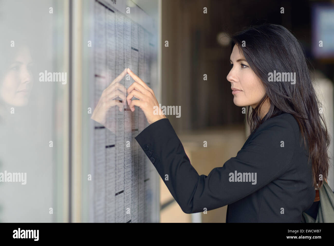 Attractive woman reading the train timetable running down the columns with her finger as she tries to find the right Stock Photo