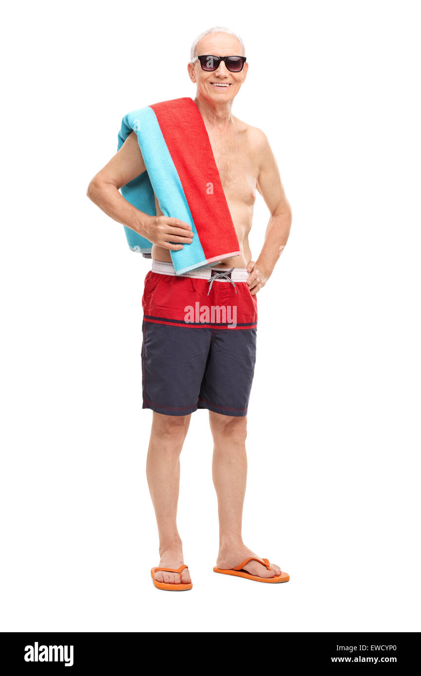 Full length portrait of a mature tourist in swim trunks holding a towel and looking at the camera isolated on white - Stock Image