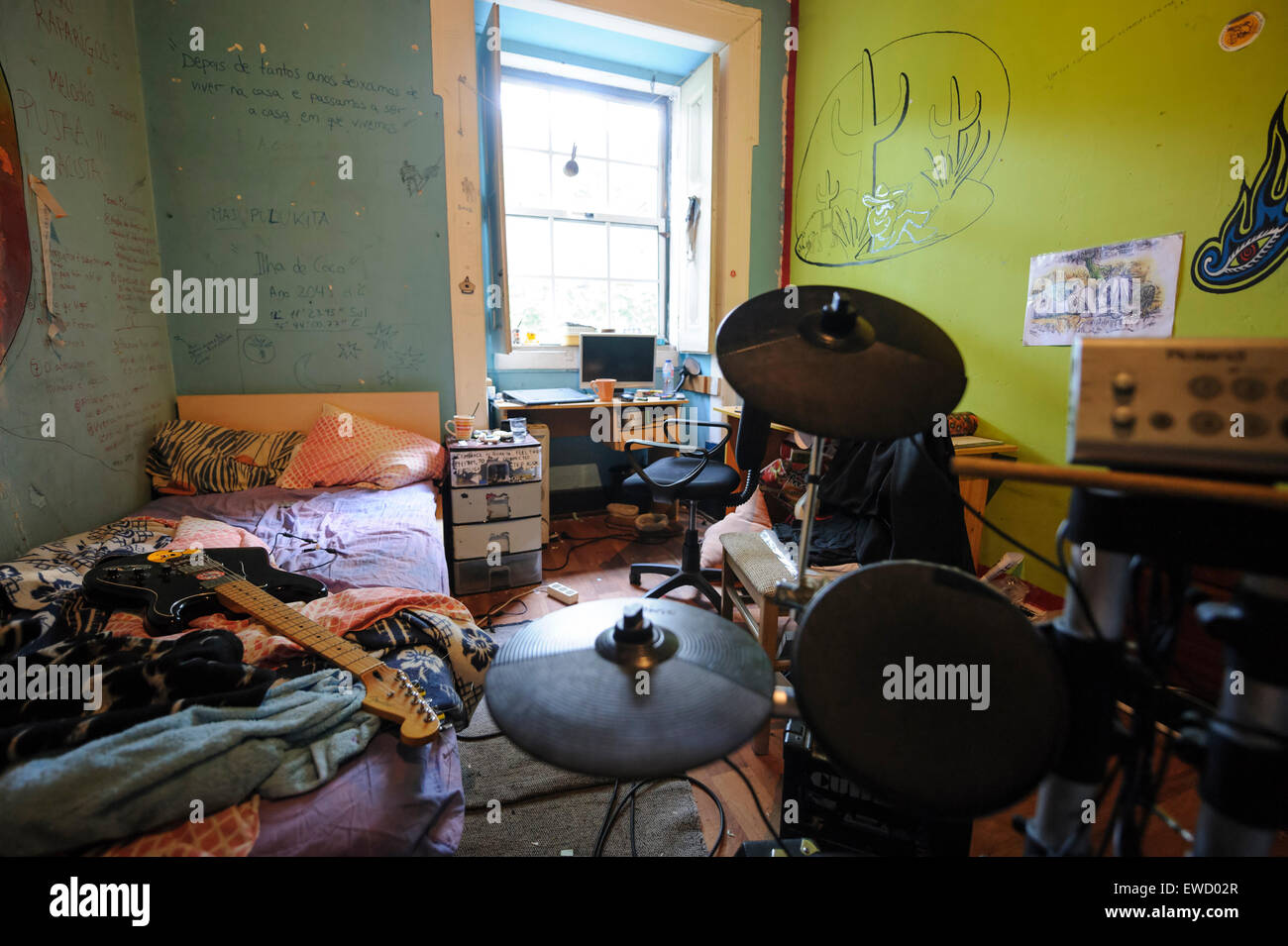 Small messy teenager bedroom with electronic drums kit and guitar on top of the unmade bed - Stock Image