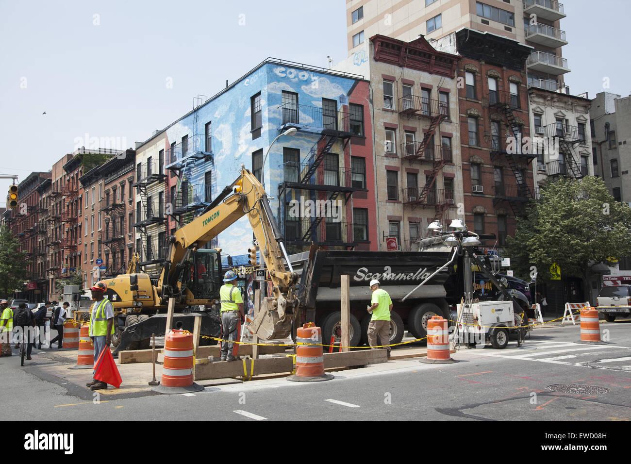 Walking along 1st Avenue passing street repair in the East Village, Manhattan, New York City. - Stock Image