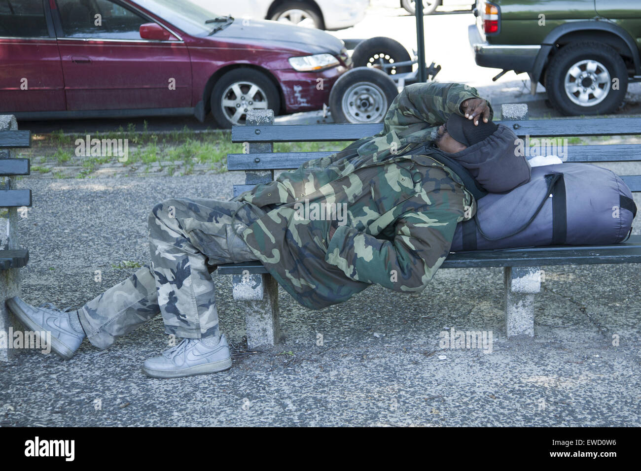 Man dressed in army camouflage uniform sleeps on a bench by Prospect Park, Brooklyn, NY. - Stock Image