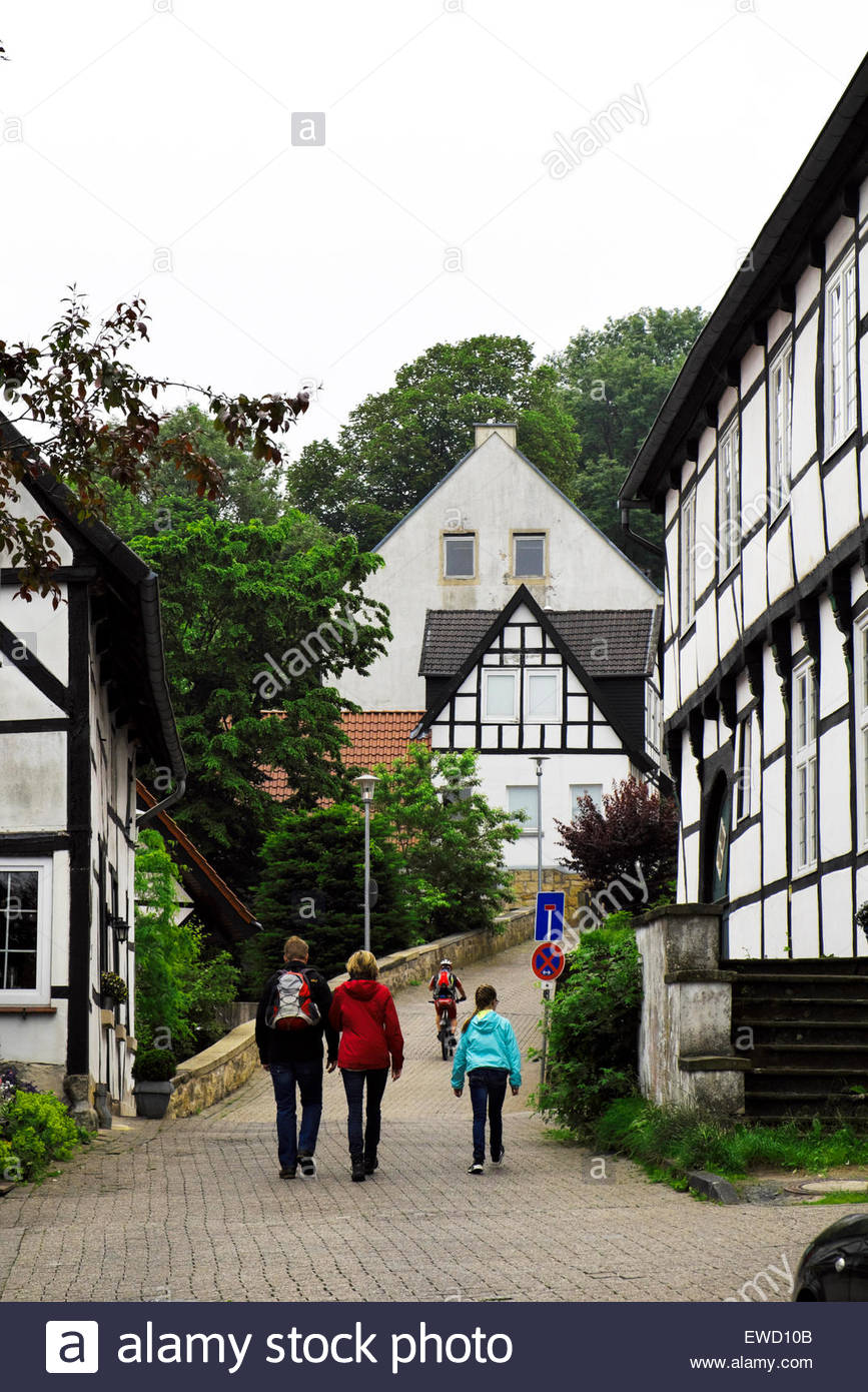 A young family strolls and a cyclist rides on a street passing between old post-and-beam houses in Tecklenburg, - Stock Image
