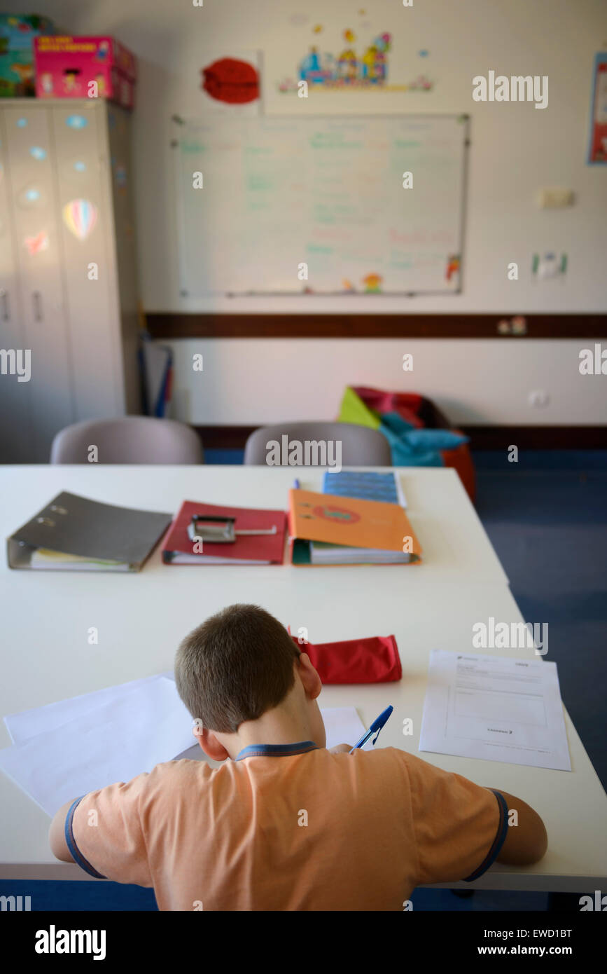 Rear view of a boy doing homework at home - Stock Image