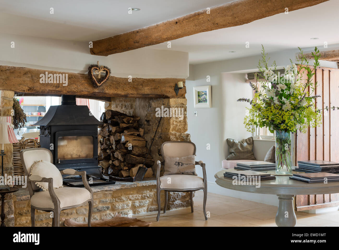 Wood burning stove in entrance hall with pair of Louis XV chairs and round console table - Stock Image