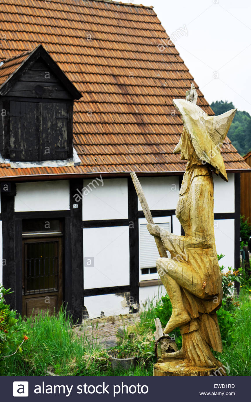 Post-and-beam house in Tecklenburg, Germany, has wood carving of witch relating to the Hexenpfad, or Witches' - Stock Image