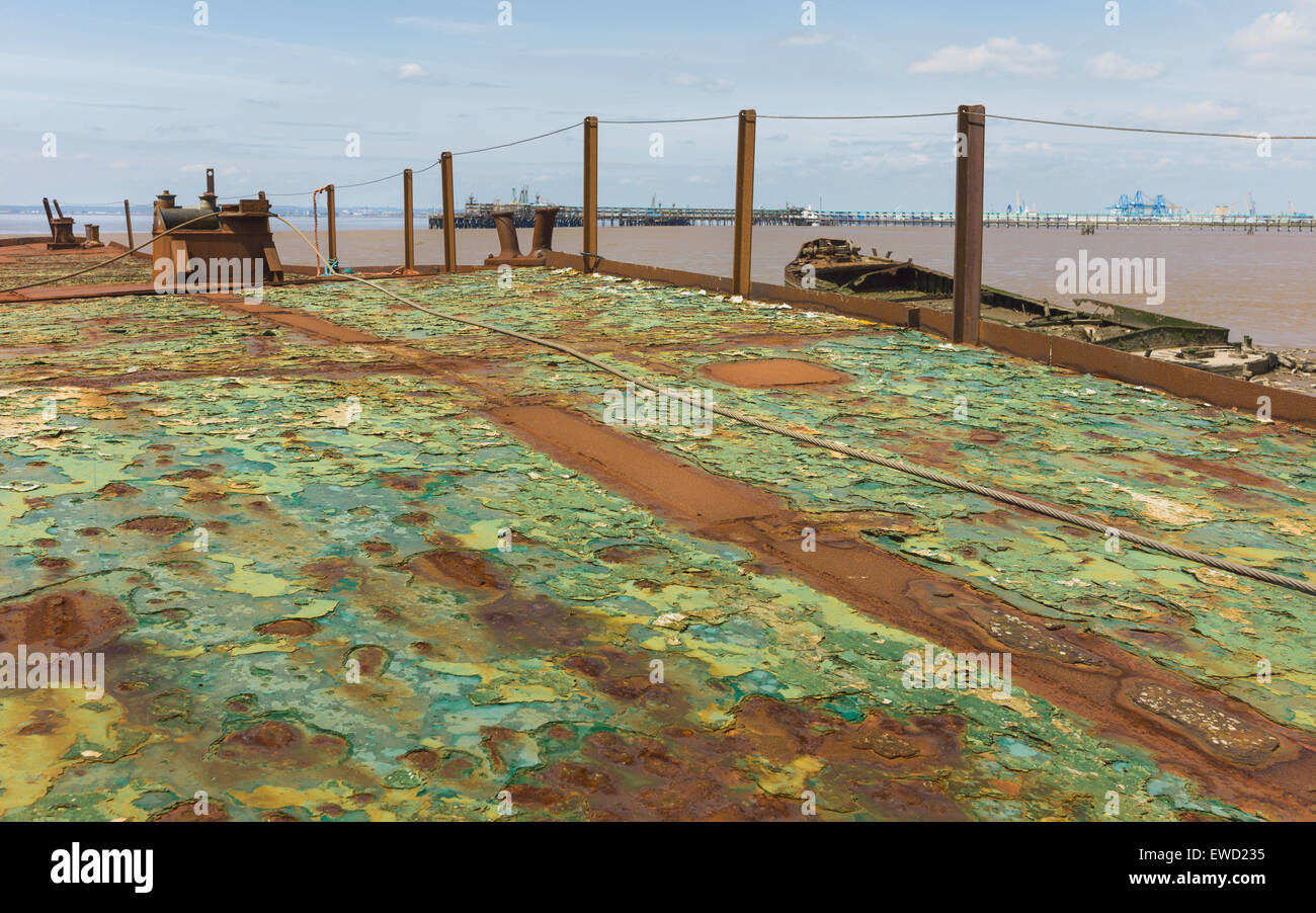 Rusting, derelict, ship deck overlooking the mud bank of the Humber estuary and other derelict boats and jetty. - Stock Image