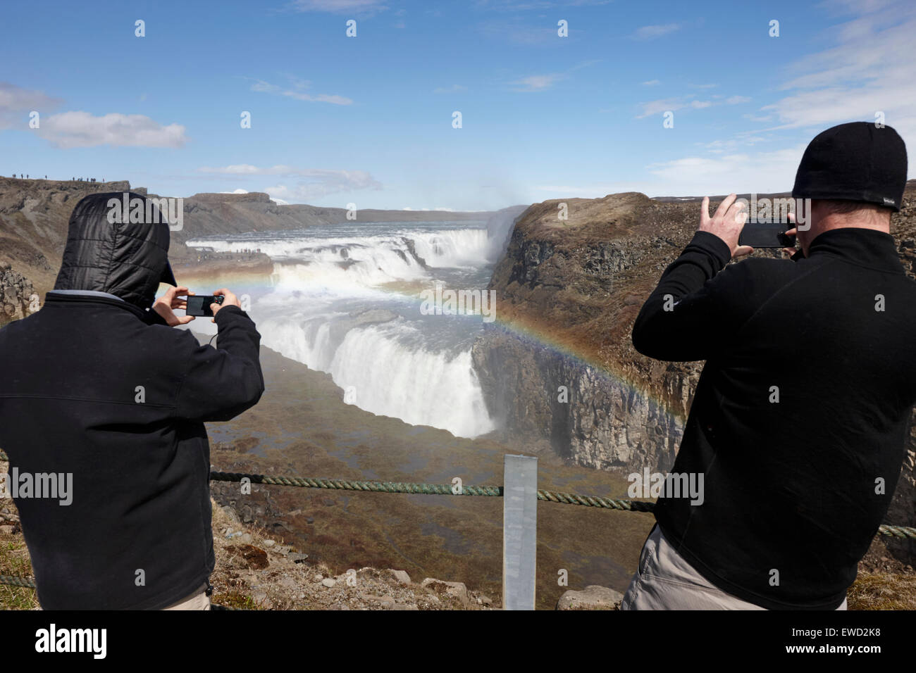 tourists taking photos with smartphones at Gullfoss waterfall Iceland - Stock Image