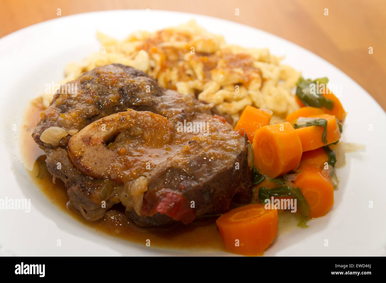 Ossobuco with spaetzle and carrots Stock Photo