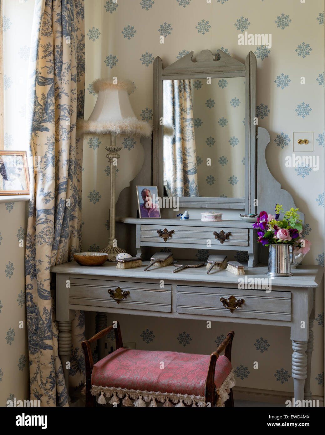 Wooden dressing table painted in Anner Sloan's French Grey while the stool is upholstered in Volga linen - Stock Image