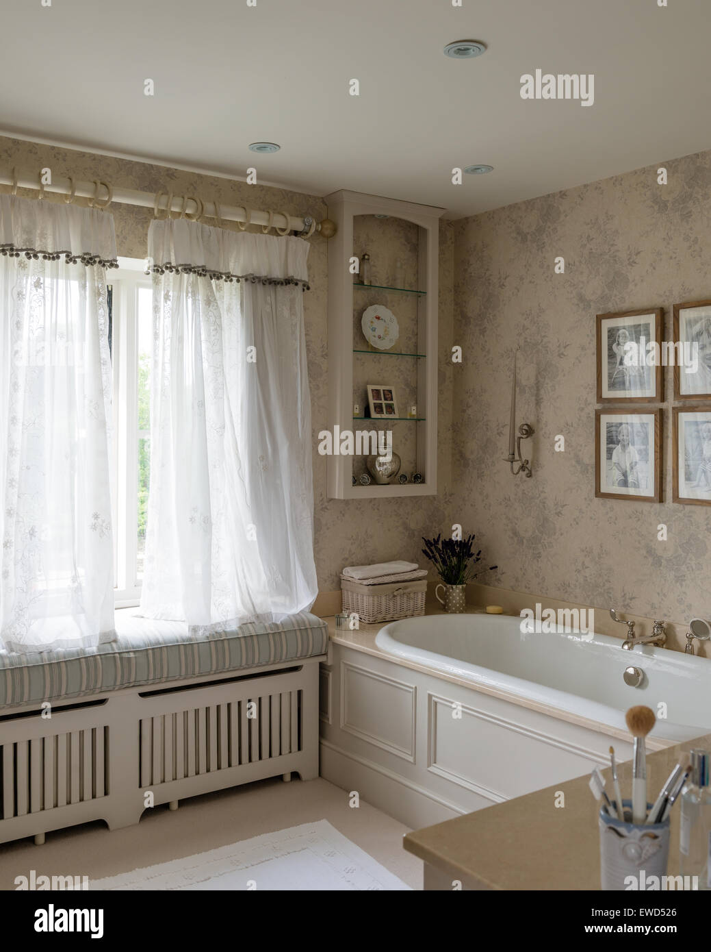 Faded grey Rose wallpaper by Kate Forman in bathroom with sheer curtains from Chelsea Textiles - Stock Image