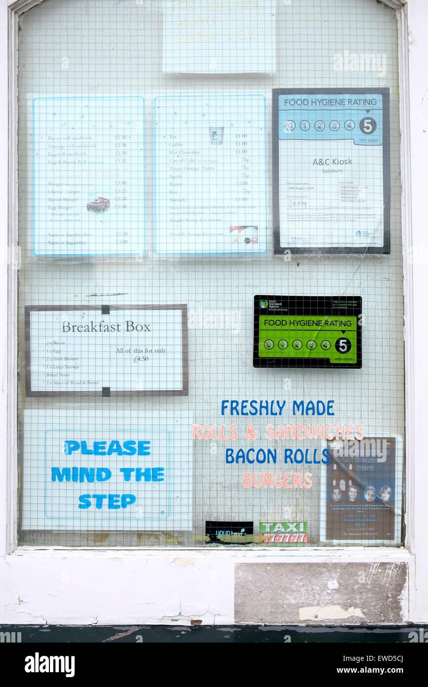 Fliers, menus and food hygiene rating sticker behind wire mesh Stock ...