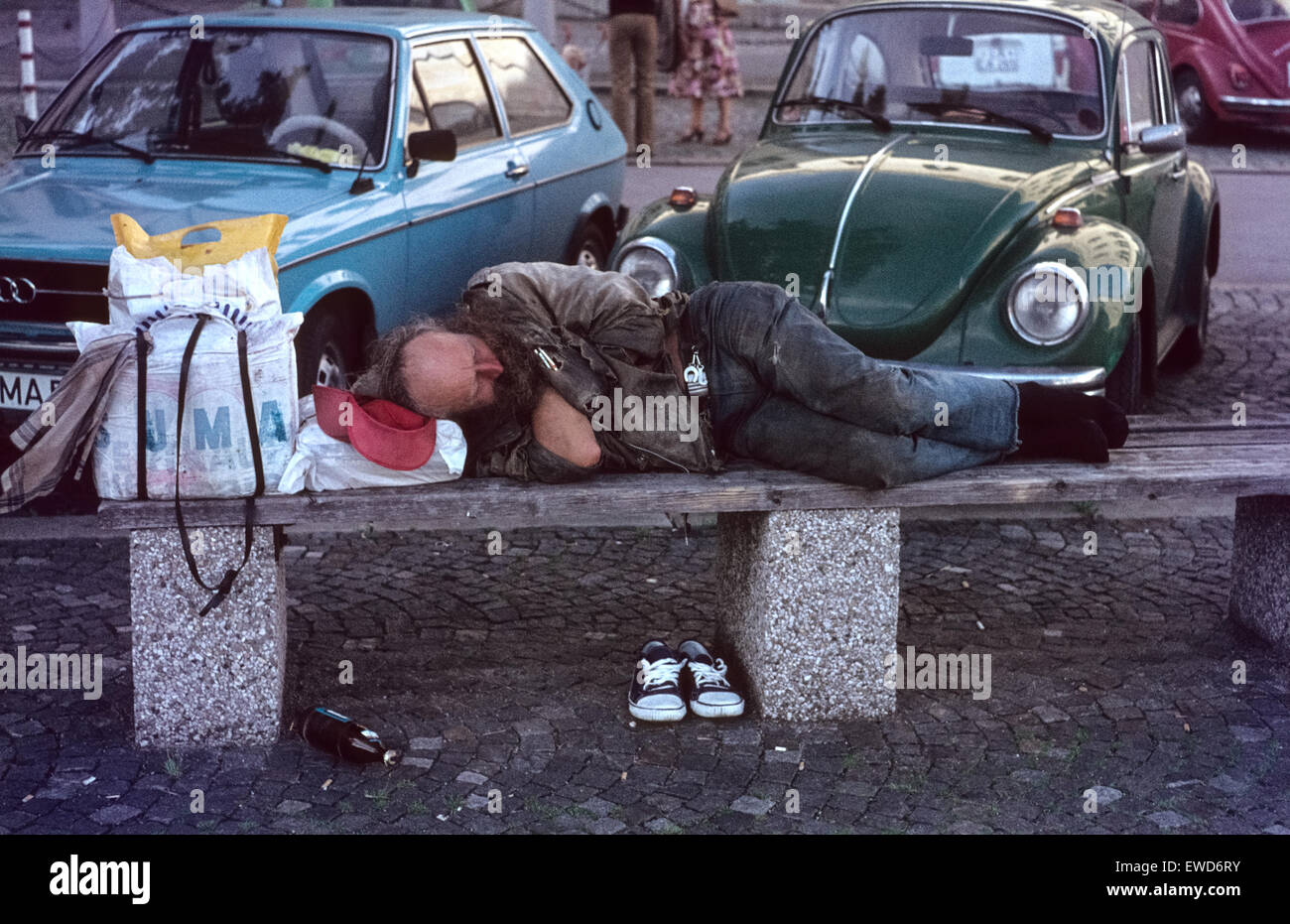 Homeless man sleeping on a bench in front of the university Munich 1978 Schlafender Obdachloser auf einer Bank in - Stock Image