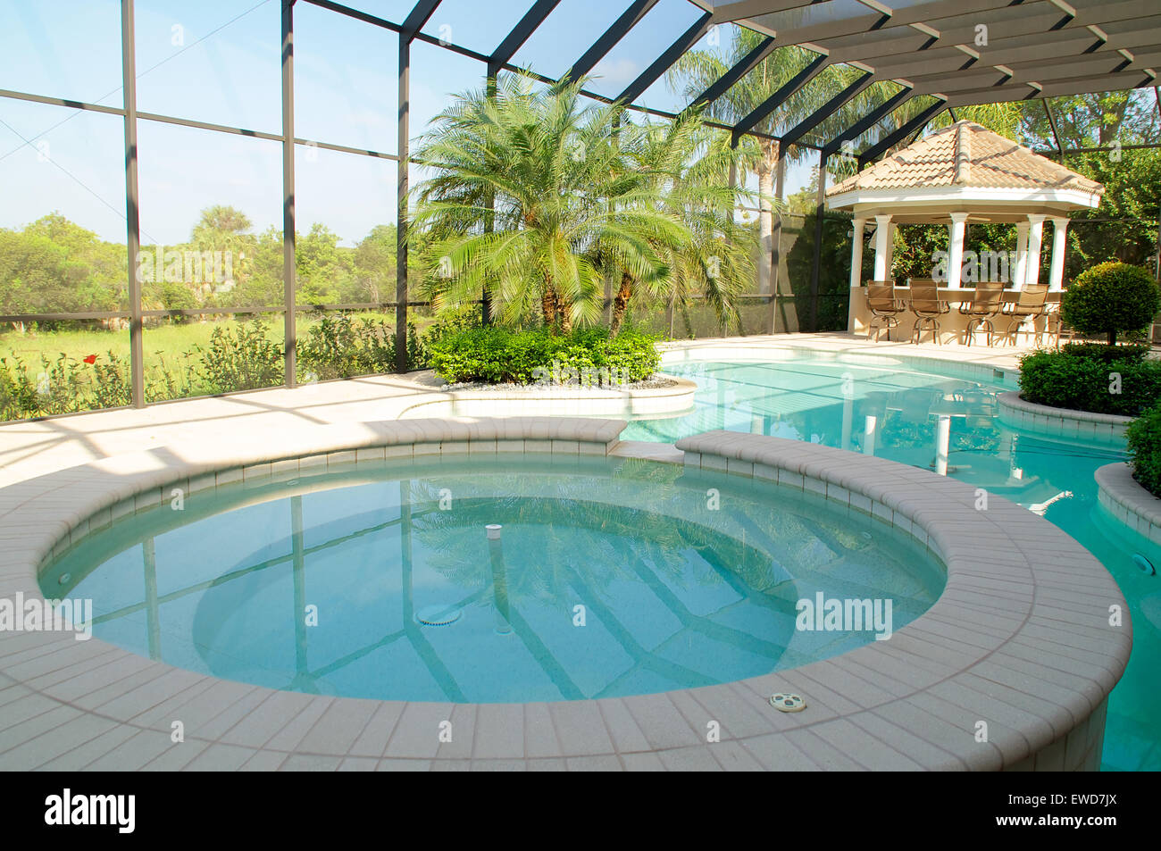 Screened in swimming pool with spa in the foreground and a ...