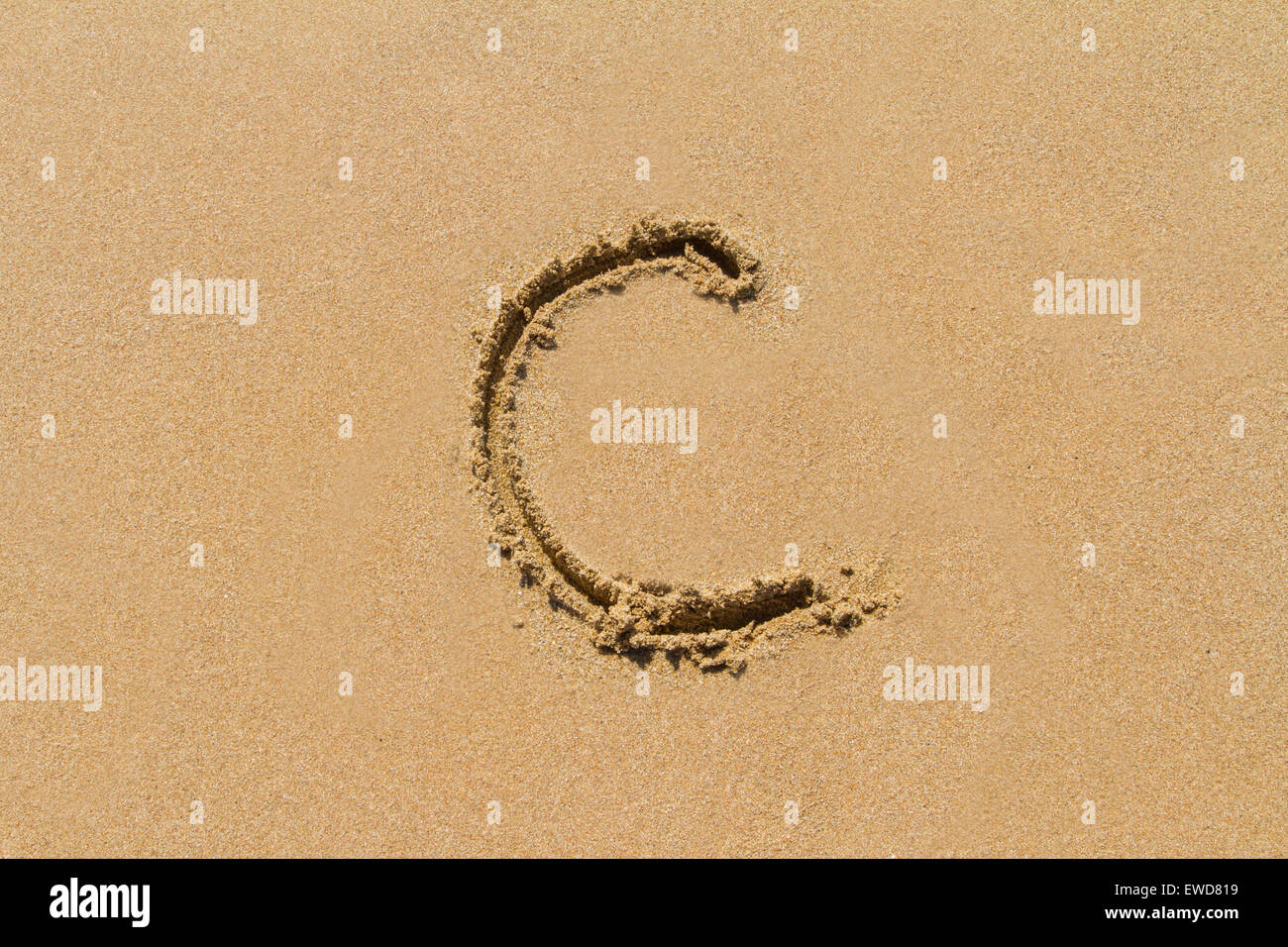 Letter C of the alphabet written on sand with upper case. - Stock Image