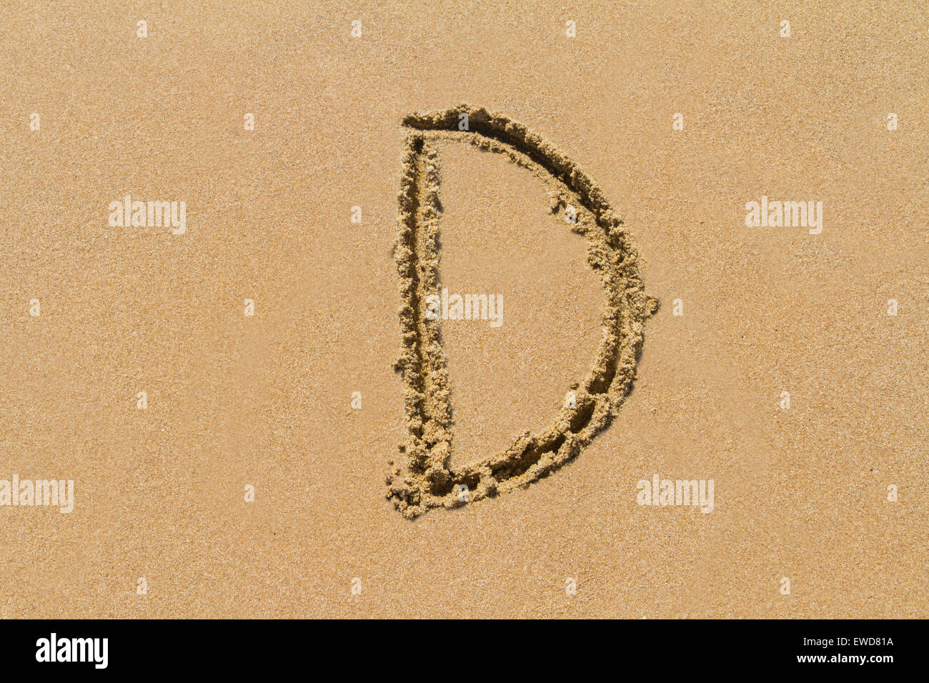 Letter D of the alphabet written on sand with upper case. - Stock Image