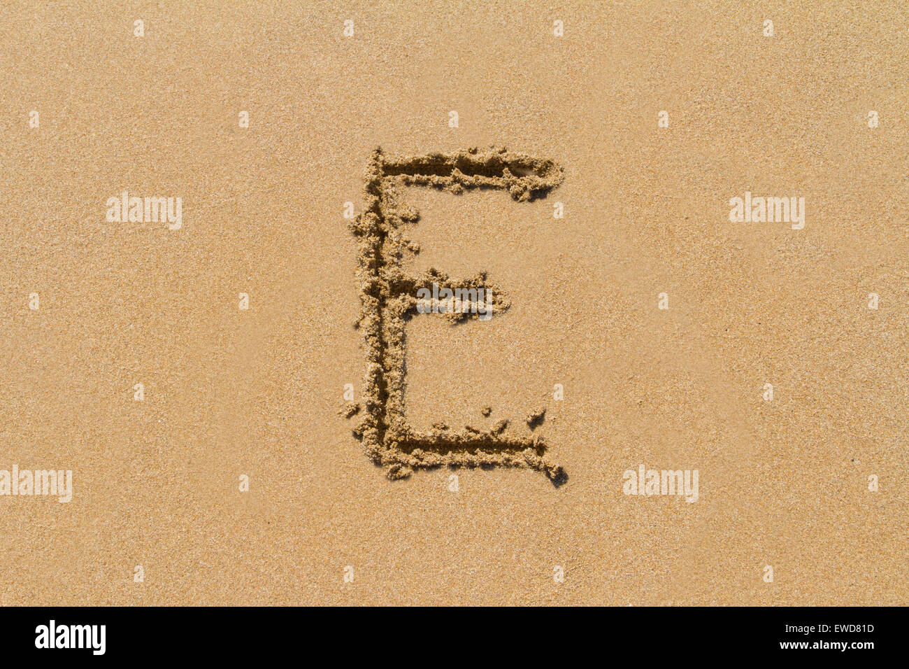 Letter E of the alphabet written on sand with upper case. - Stock Image