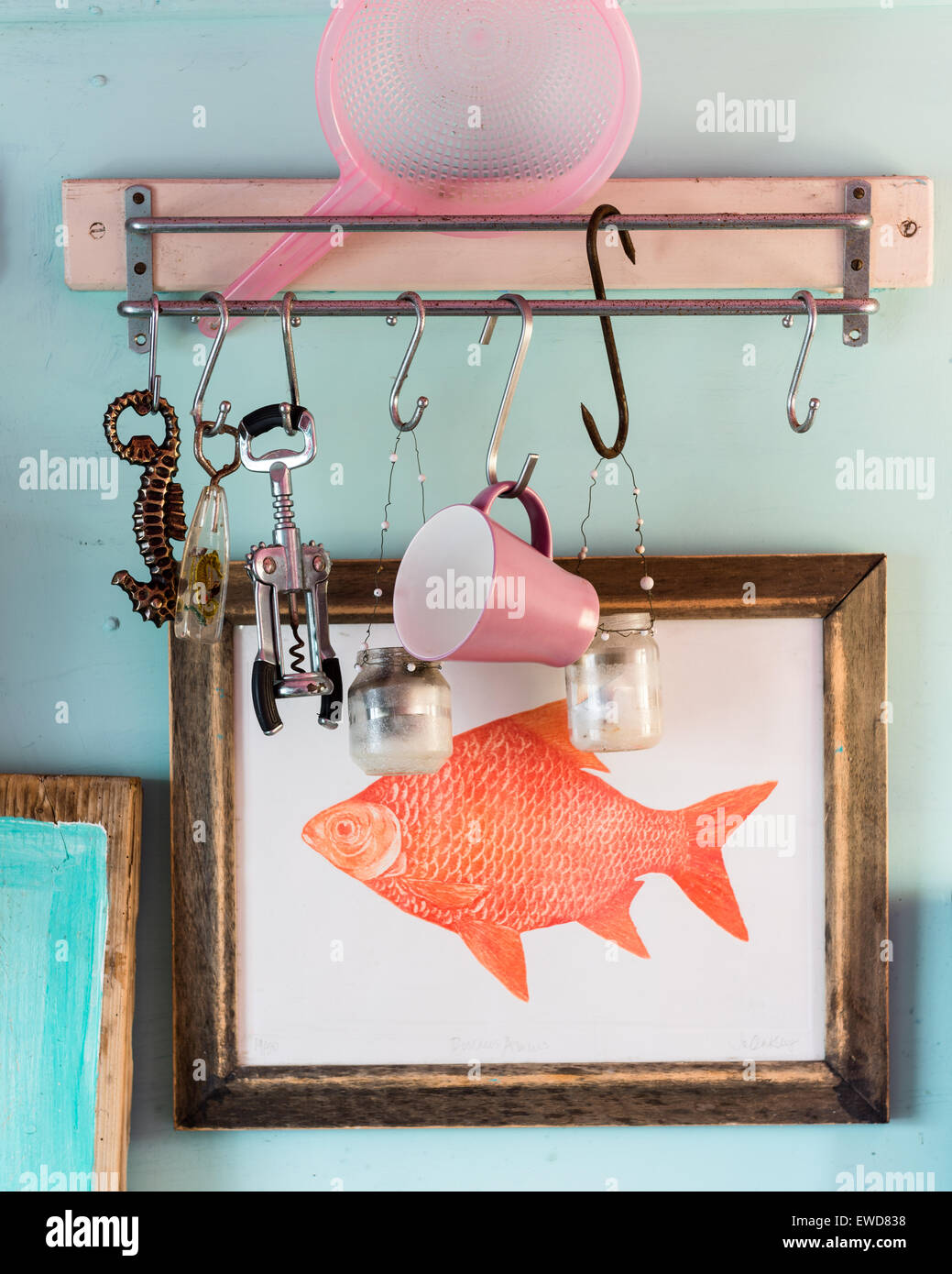 Candle holders and bottle openers hanging from hooks on wall above framed goldfish artwork - Stock Image