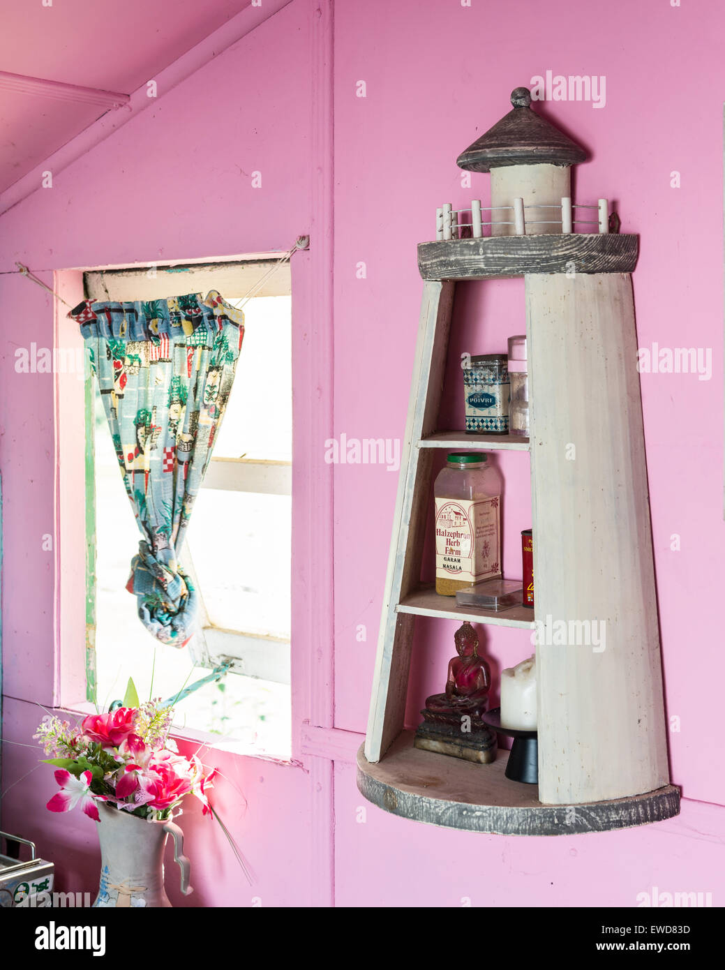 Lighthouse shaped shelf on pink wall of beach hut with vintage curtain - Stock Image