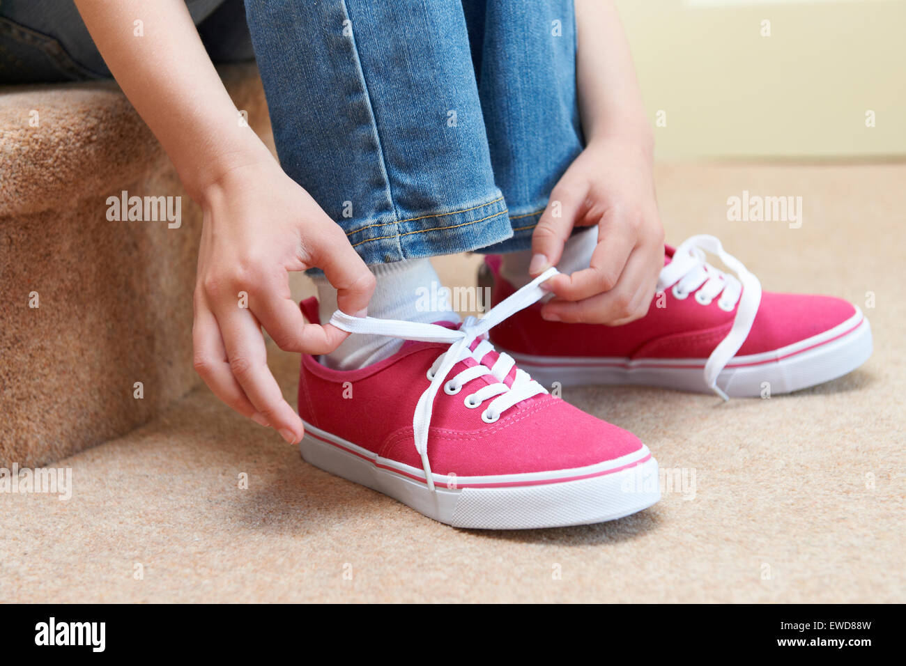 Girl Sitting On Stairs And Tying Shoelaces - Stock Image