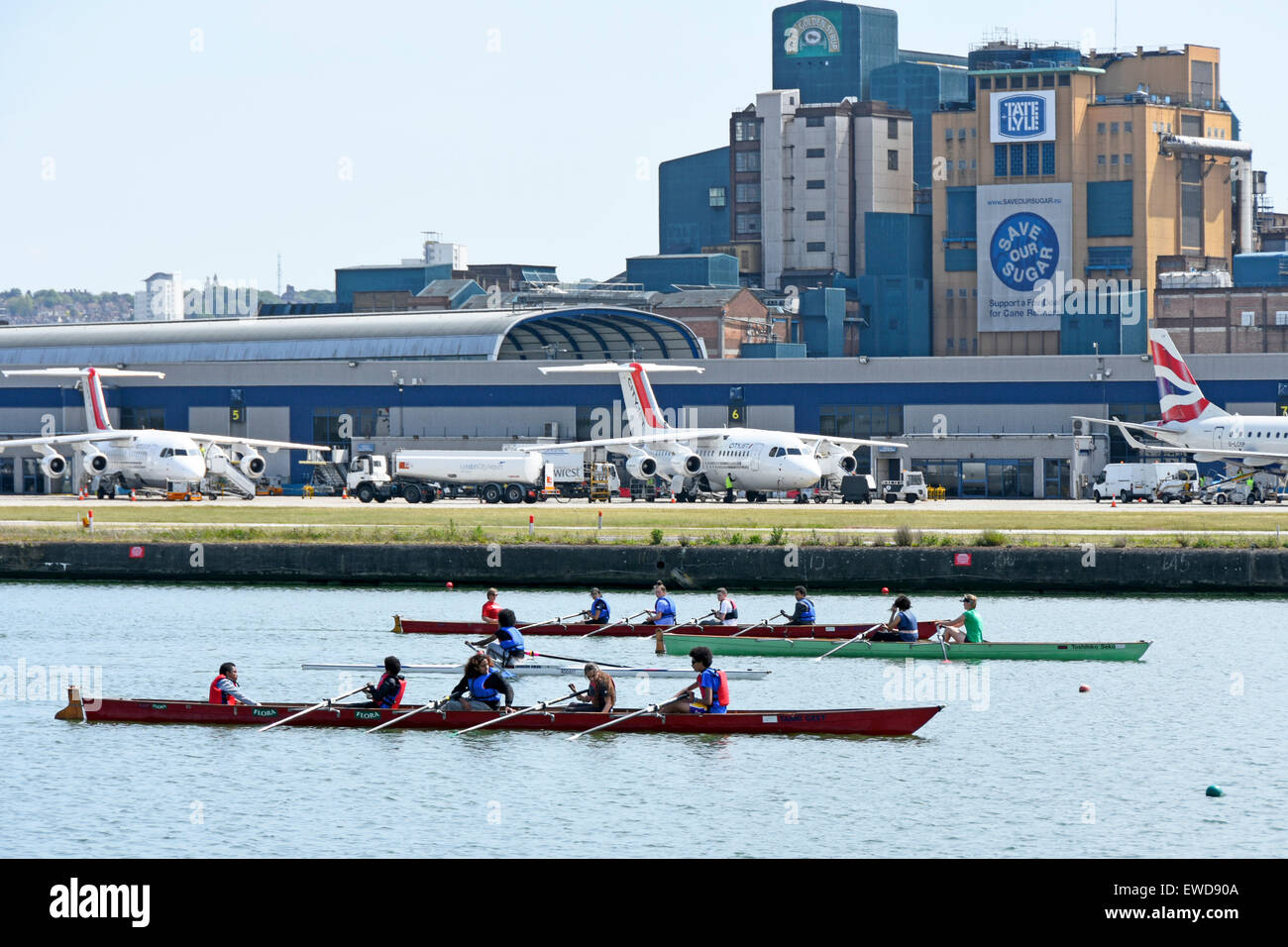 Airplane at London City Airport rowers training in old Royal Docks next to runway London Docklands Newham England Stock Photo