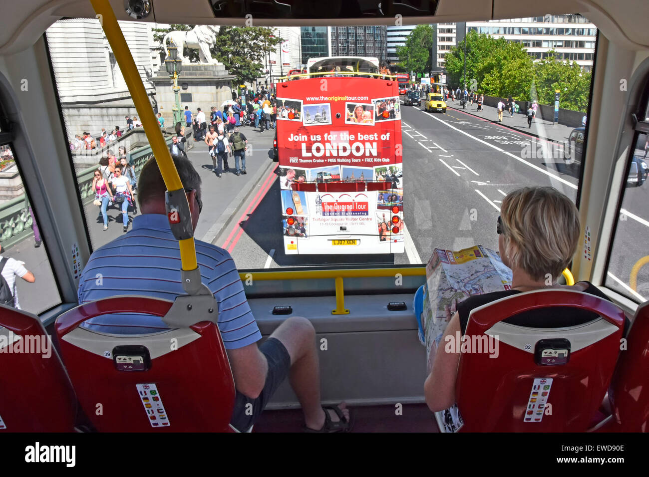 Tourist holds map sitting front seats on top deck of tour bus crossing River Thames on Westminster Bridge more tour - Stock Image