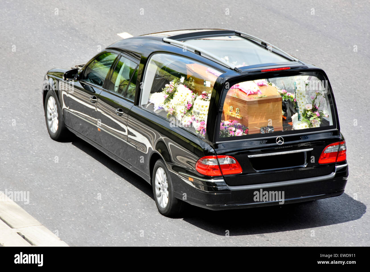 Coffin in funeral hearse floral tributes obscured numberplate with coffin in funeral hearse floral tributes obscured numberplate with one brass decoration removed view from above looking down from bridge england uk izmirmasajfo