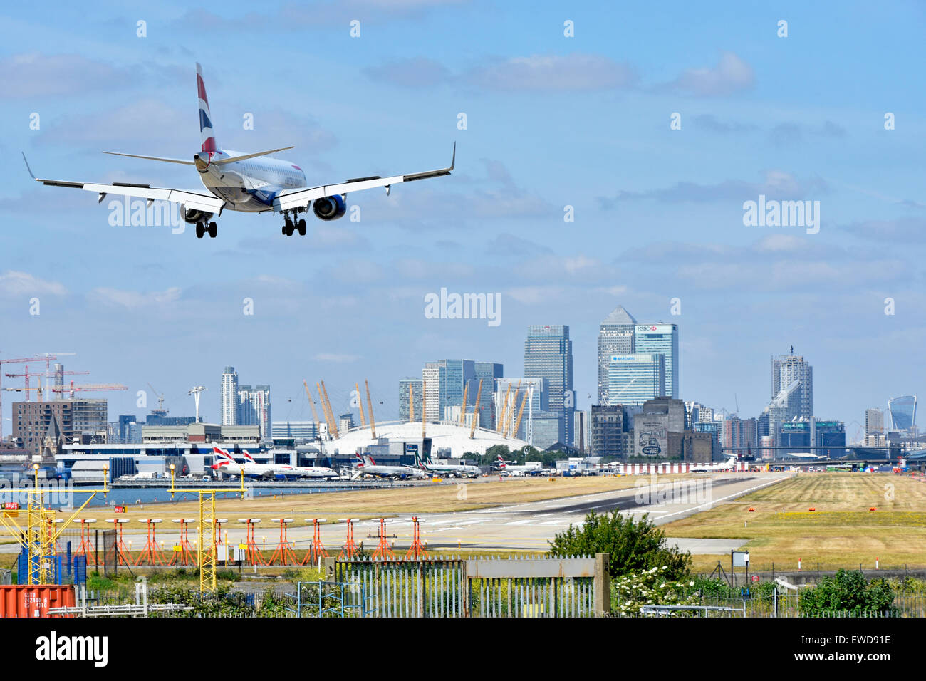 British Airways airplane landing London City Airport Newham with O2 arena & Canary Wharf in London Docklands - Stock Image