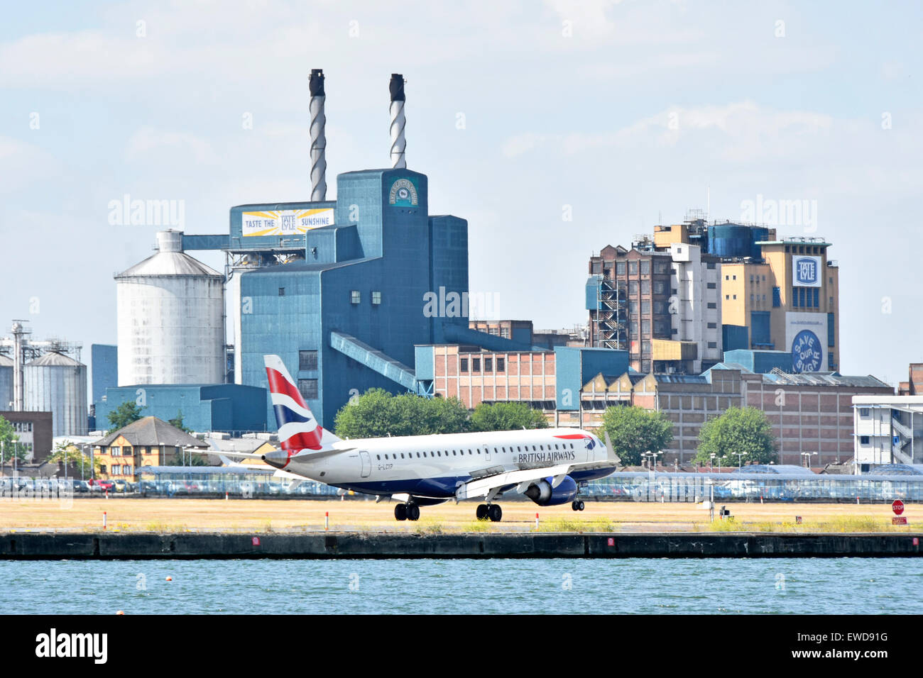 British Airways flight landing at London City Airport with Tate and Lyle Silvertown sugar refinery factory buildings - Stock Image