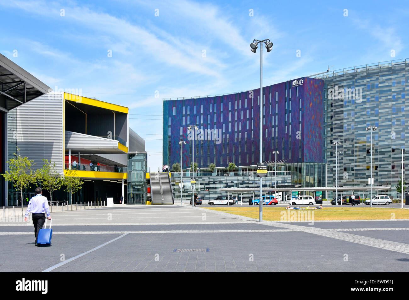 Business man walking towards exhibition hall eastern entrance of London Excel centre left yellow & adjacent - Stock Image