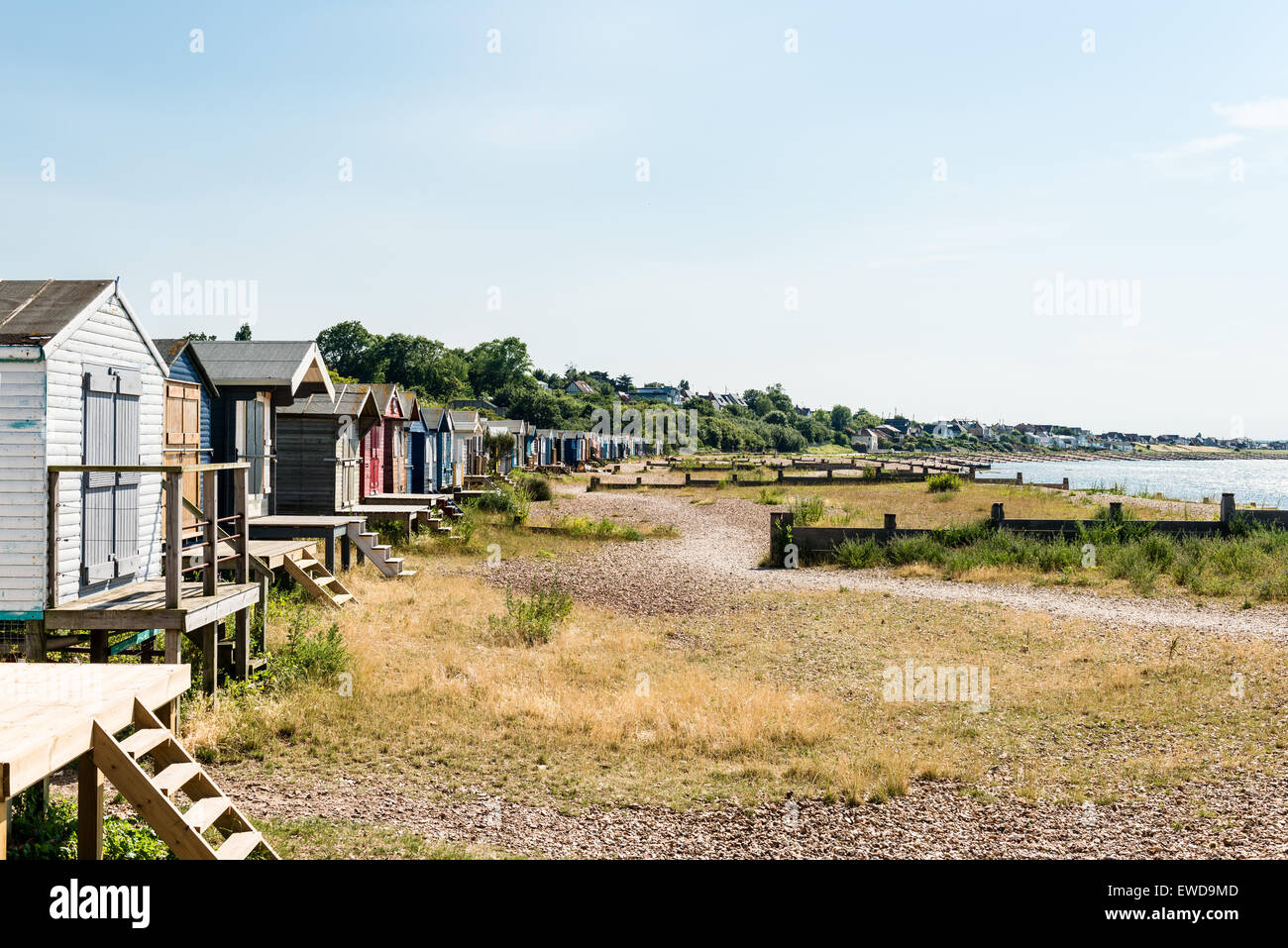 Row of wooden beach huts along Whitstable beach Stock Photo