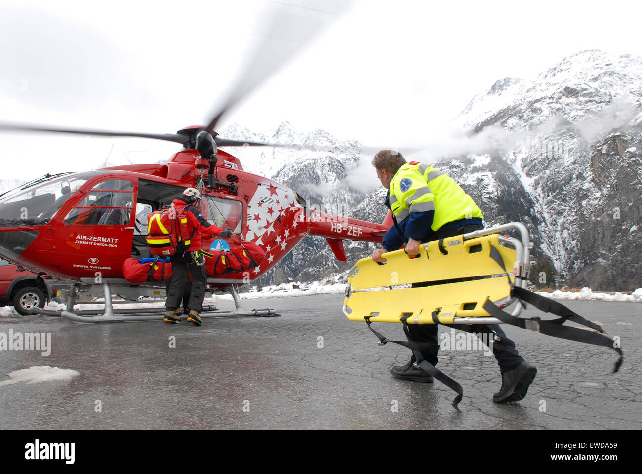 An ambulance paramedic is walking to a rescue helicopter to help an injured mountaineer that was flown down from - Stock Image
