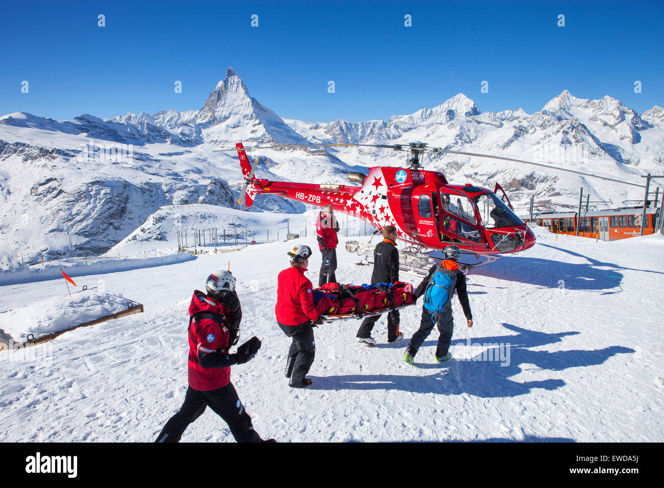 Rescue personnel are carrying an injured skier to a helicopter of Air Zermatt at the Gornergrat ski area in Zermatt - Stock Image