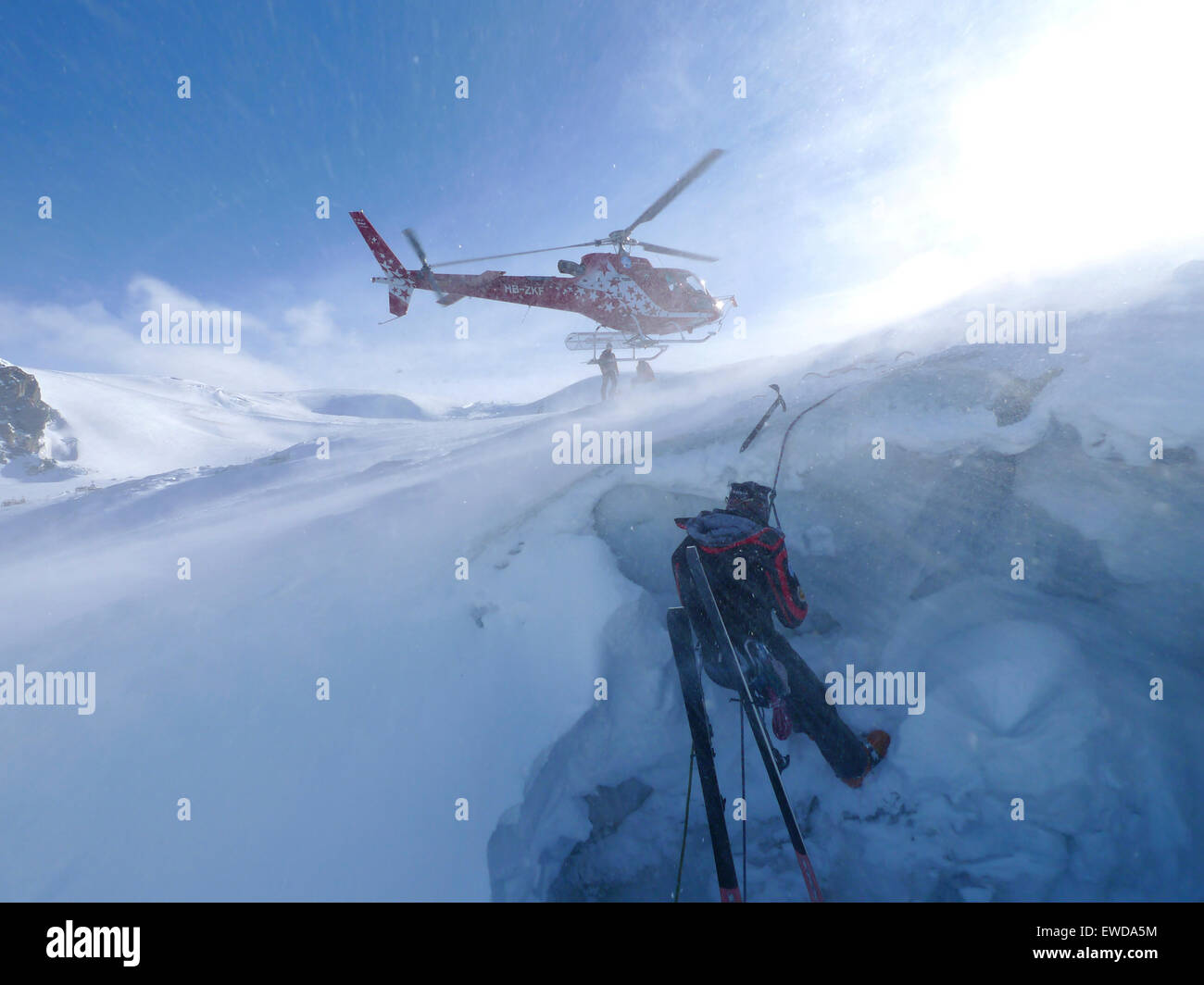 A mountain rescue technician is descending into a crevasse. When a skier breaks through the snow and tumbles down - Stock Image