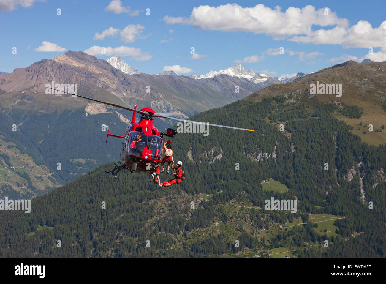 A mountain rescue emergency physician is hanging below a helicopter high above the ground. A injured hiker is being - Stock Image