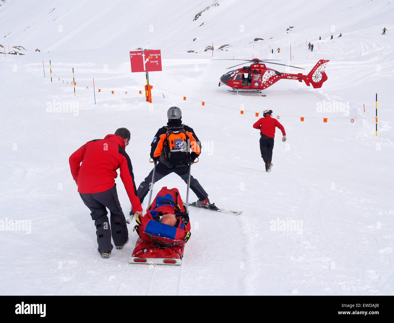 Rescue Personnel is helping an injured skier in the ski area of Zermatt in the Swiss Alps. - Stock Image