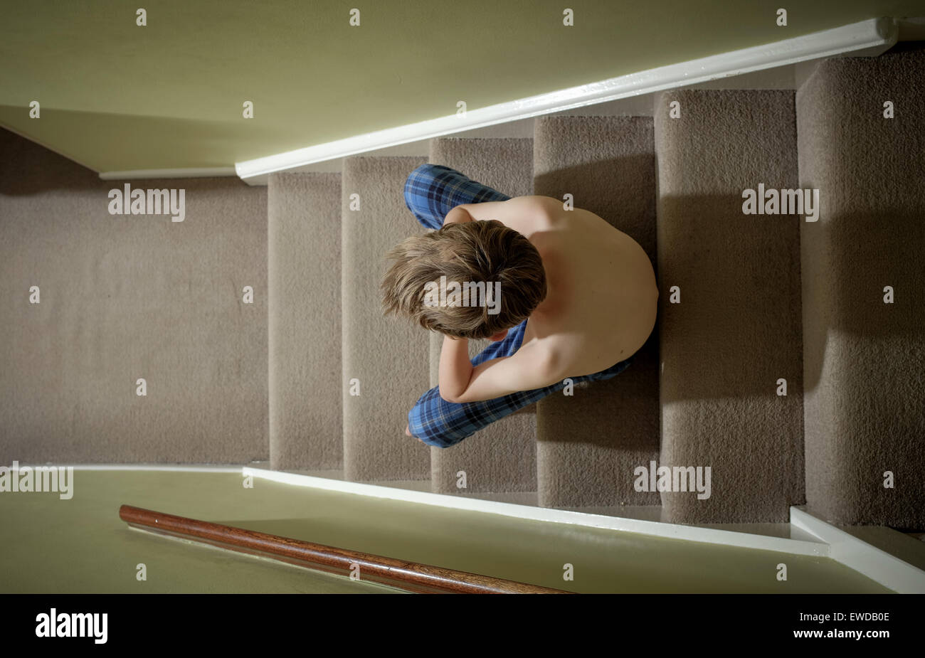 A child sitting on the stairs with his head in his hands looking upset Stock Photo