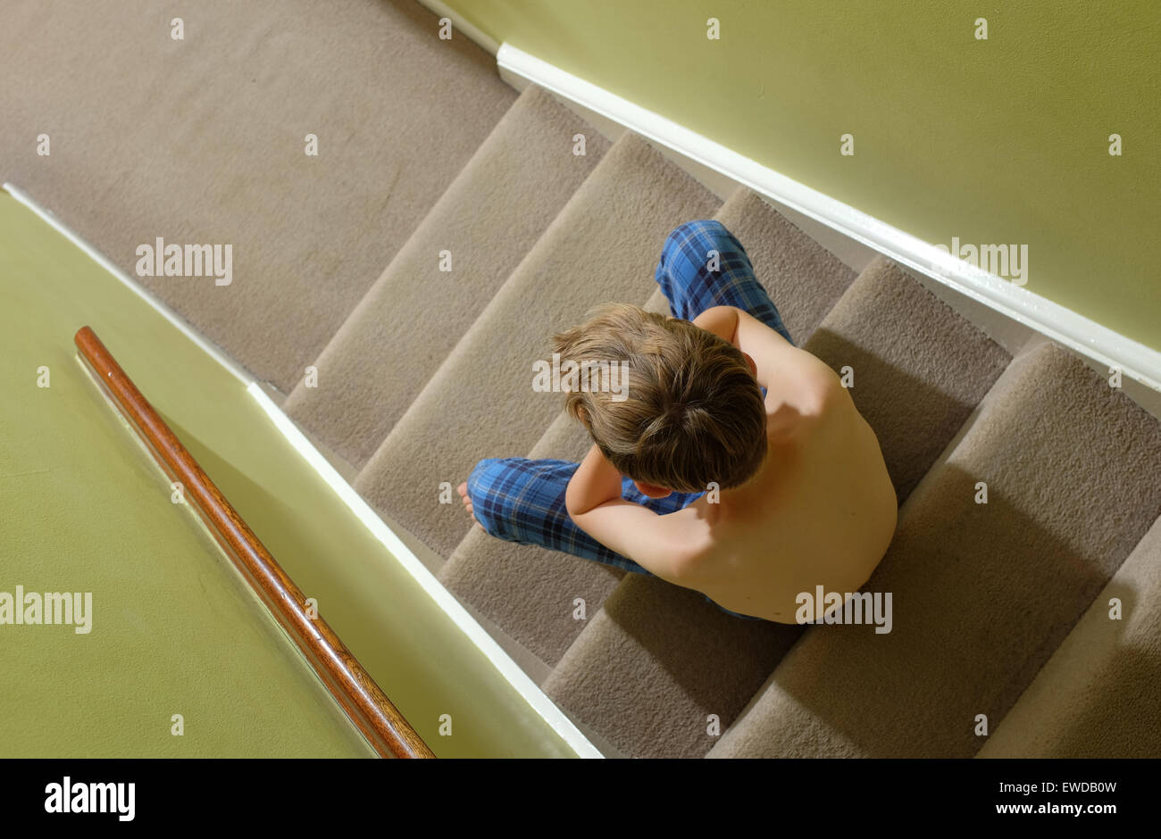 A child sitting on the stairs with his head in his hands looking upset - Stock Image