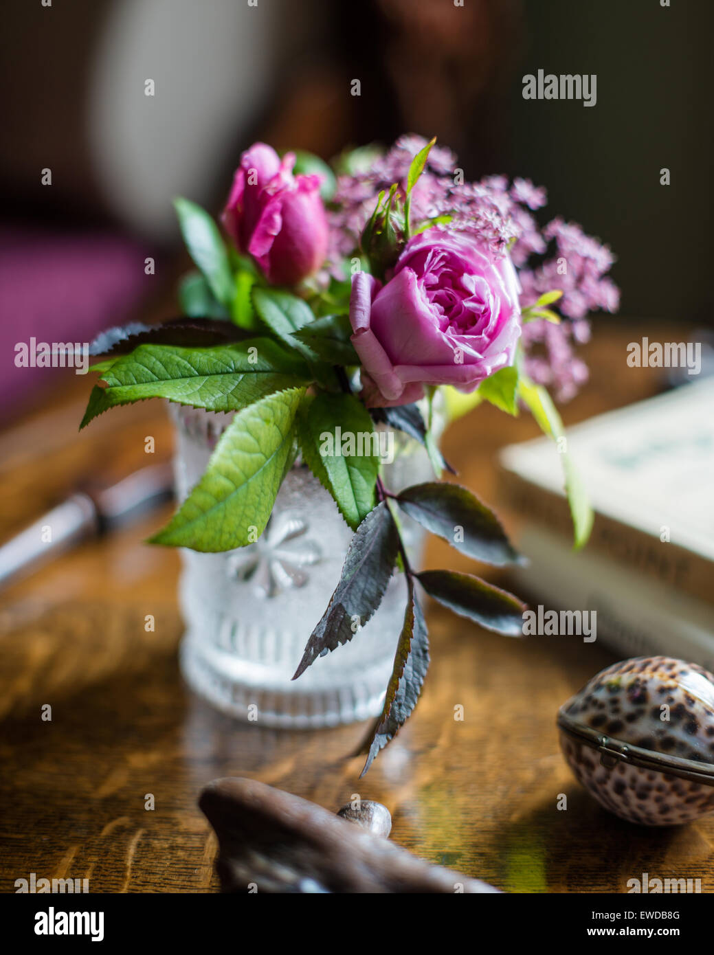 Posy of roses in glass tumbler - Stock Image