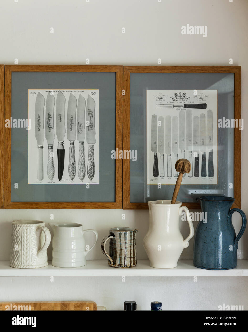 Assorted ceramic jugs on shelf underneath old fashioned framed prints of knives - Stock Image