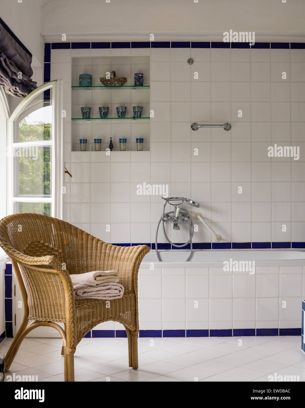 Wicker chair in tiled bathroom Stock Photo - Alamy