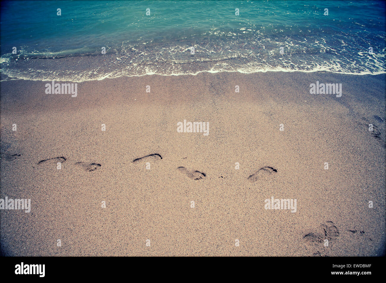 fd8660563 Footsteps in the sand at the beach - retro styled photo - Stock Image